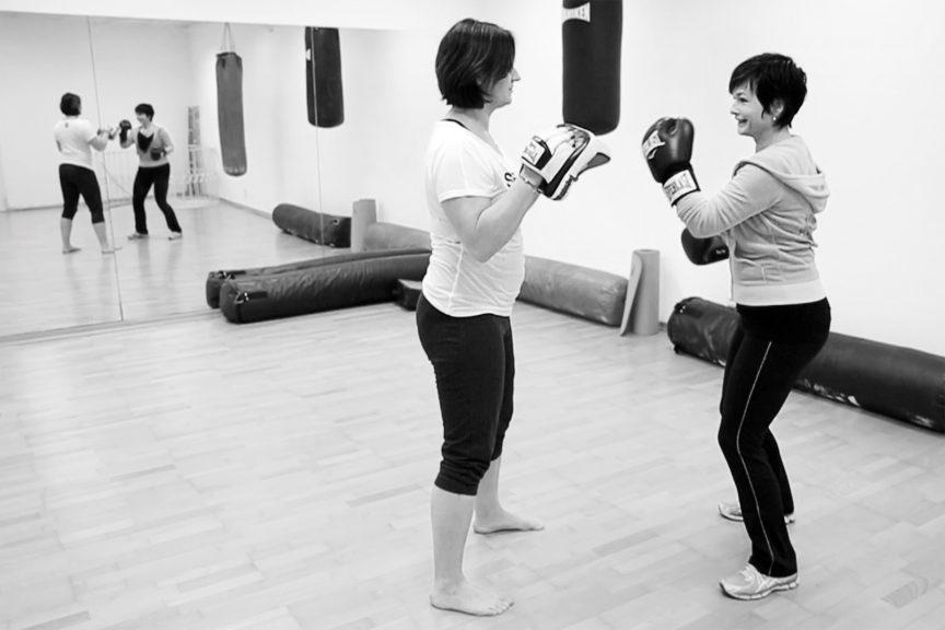 Zwei Frauen beim Boxtraining, eine mit Pratzen, eine mit Handschuhen